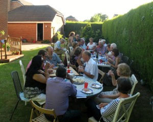 Guests sought the shade of the tall hedge from the heat of the early evening sun.